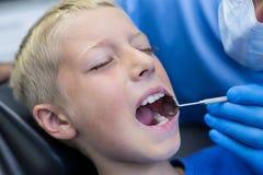 审查有工具的牙医一名年轻患者 免版税图库摄影