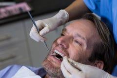审查有工具的牙医一名年轻患者 库存照片