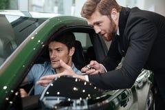 审查有推销员的年轻人一辆新的汽车 库存图片