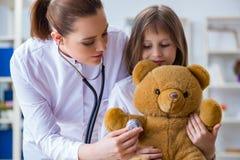 审查有玩具熊的妇女女性医生小逗人喜爱的女孩 免版税库存照片