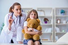 审查有玩具熊的妇女女性医生小逗人喜爱的女孩 免版税库存图片