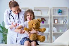 审查有玩具熊的妇女女性医生小逗人喜爱的女孩 图库摄影