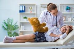 审查有玩具熊的妇女女性医生小逗人喜爱的女孩 库存照片