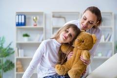 审查有玩具熊的妇女女性医生小逗人喜爱的女孩 库存图片