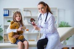 审查有玩具熊的妇女女性医生小逗人喜爱的女孩 免版税图库摄影