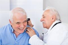 审查有耳镜的医生老人的耳朵 免版税库存照片