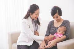 审查母亲la的亚裔女性儿科医生一个女婴 库存图片