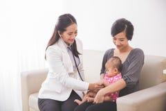审查母亲la的亚裔女性儿科医生一个女婴 免版税库存照片
