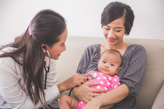 审查母亲la的亚裔女性儿科医生一个女婴 免版税图库摄影