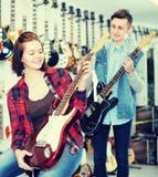 审查电吉他的两名青年人顾客 免版税图库摄影