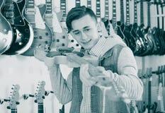 审查电吉他的男性少年 图库摄影