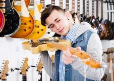 审查电吉他的男性少年 免版税库存图片