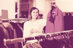 审查红色羊毛外套的好女性顾客 库存照片