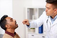 审查耐心喉头的医生在诊所 库存图片