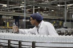 审查被装瓶的水的工厂劳工 免版税库存图片