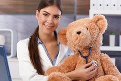 审查软的玩具的年轻医生 免版税库存照片