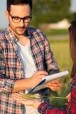 审查麦子植物词根的两位严肃的年轻女性和男性农夫或农艺师在拿着h的收获妇女前植物 免版税图库摄影