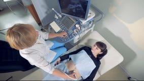 审阅与一位女性妇产科医师的超生波检查法会议的一名孕妇的顶视图 影视素材