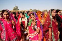 审阅人群的红色莎丽服的美丽的妇女 免版税库存照片