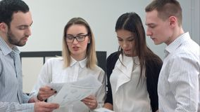 审阅企业介绍的四个年轻办公室工友 免版税库存照片