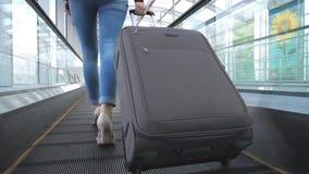 审阅终端大厅的女商人的腿有她的行李的 高跟鞋的少女走在自动扶梯的 股票视频