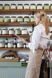 审阅香料名单的资深女性雇员侧视图在商店 免版税库存照片