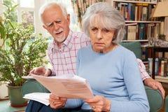 审阅财务的资深夫妇看起来担心 免版税库存照片
