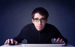 黑客与在蓝色背景的键盘一起使用 免版税图库摄影
