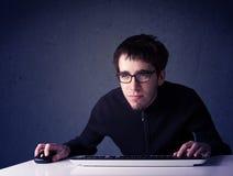 黑客与在蓝色背景的键盘一起使用 图库摄影