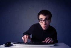黑客与在蓝色背景的键盘一起使用 免版税库存图片