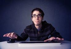 黑客与在蓝色背景的键盘一起使用 库存图片