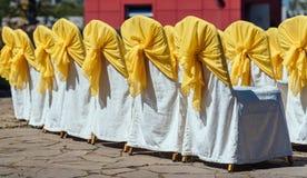 客人的椅子与室外白色和黄色缎的布料的婚礼的 免版税库存图片