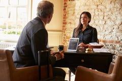 客人谈话与妇女在旅馆登记书桌 免版税图库摄影