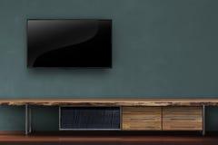客厅带领了在深绿墙壁上的电视有木桌媒介fu的 免版税库存图片
