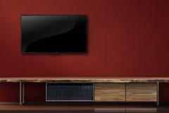 客厅带领了在红色墙壁上的电视有木桌现代顶楼猪圈的 免版税图库摄影