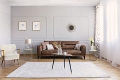 客厅最小的室内设计有棕色皮革长沙发、减速火箭的扶手椅子咖啡桌和金黄装饰的 图库摄影