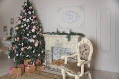 客厅的内部有壁炉的,装饰与一棵大圣诞树和许多的新年礼物 免版税库存图片