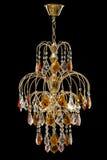 客厅的内部的枝形吊灯 用水晶装饰的在黑背景隔绝的枝形吊灯和琥珀 图库摄影