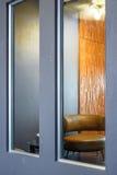 客厅角落的反射与棕色圆的沙发和灰色墙壁的 免版税库存照片