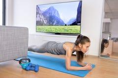 客厅锻炼-在家做板条的女孩 免版税图库摄影