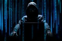黑客在膝上型计算机后坐 库存照片
