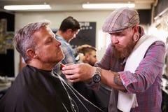 给客户刮脸的男性理发师在商店 库存照片