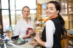 客户在支付在收款机的商店 图库摄影