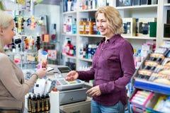 客户在支付在收款机书桌的商店 库存照片