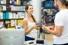 客户在支付在收款机书桌的商店 免版税库存照片