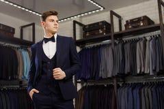 客户是尝试在一套衣服的典雅的人在镜子商店 在背景经典衣服和夹克 库存图片