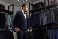 客户是尝试在一套衣服的典雅的人在镜子商店 在背景经典衣服和夹克 免版税库存照片