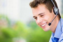 客户服务代表或电话中心代理或者支持或者操作员有耳机的在外部阳台 库存照片