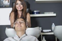客户的一根年轻美发师洗涤的头发的Portait 库存图片