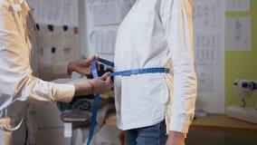 客户的腰部的被聚焦的年轻设计师测量的大小使用卷尺的 影视素材
